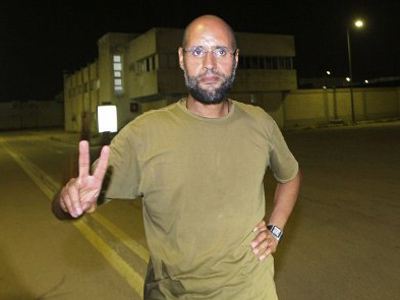 Saif al-Islam Gaddafi, son of Libyan leader Muammar Gaddafi, flashes the V-sign for victory as he appears in front of journalists at his father's residential complex in the Libyan capital Tripoli in the early hours of August 23, 2011 (AFP Photo / Imed Lamloum)