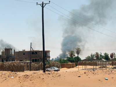 Black smoke billows as fighting takes place in the southern oasis city of Kufra, located in a triangle where the borders of Egypt, Chad and Sudan meet, on June 12, 2012, as members of Libya's Toubou minority and government forces clash AFP Photo / Str