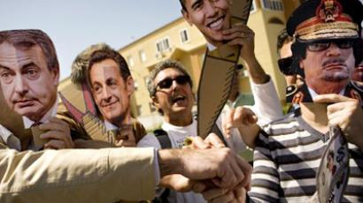 "Protesters wearing masks featuring (L-R) Spanish Prime Minister Jose Luis Rodriguez Zapatero, French President Nicolas Sarkozy, US President Barack Obama, Libyan leader Moamer Kadhafi take part in an anti-war demonstration calling on governments to ""stop bombing Libya"" in front of the Base Naval de Rota (AFP Photo / Jorge Guerrero)"