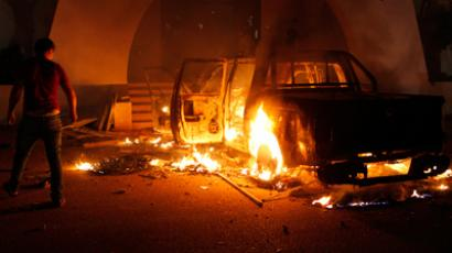 A demonstrator stands next to a burning car which the demonstrators set alight and said was full of ammunition as they stormed the HQ of the Islamist Ansar al-Sharia militia group in Benghazi September 21, 2012 (Reuters)