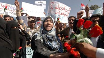 A Yemeni woman hands out roses during a protest in Sanaa. (AFP Photo / Mohammed Huwais)