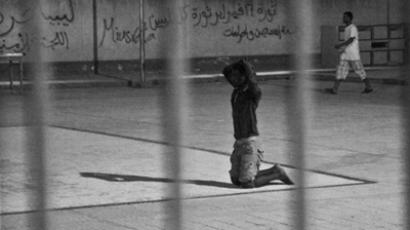 "A detainee at a Misrata detention facility is forced to crawl on his knees. ""We do this every day. It is sport before they go to bed. They committed rape,"" one of the guards said on September 25, 2011© 2011 Sidney Kwiram / Human Rights Watch"
