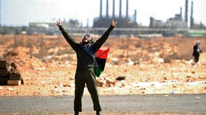 "A Libyan rebel fighter wearing his old national flag as a cape flashes the ""victory"" sign as he looks at an airforce fighter jet flying overhead at a checkpoint on the outskirts of the oil town of Ras Lanuf (AFP Photo / Getty Images)"