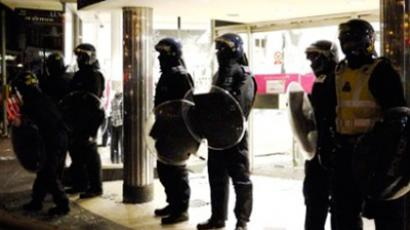 Riot police protect the entrance to a department store in Clapham Junction, south London (AFP Photo / Leon Neal)