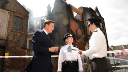 United Kindom, London : British Prime Minister David Cameron talks to police officers including Acting Borough Commander Police Superintendent Jo Oakley in Croydon, south of London, on August 9, 2011.  (AFP Photo / Stefan Rousseau)