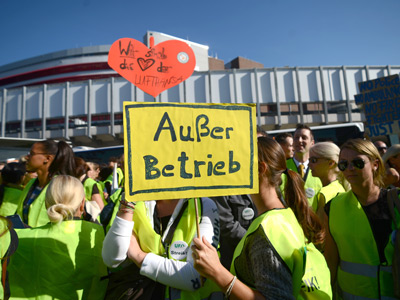 "A German airline Lufthansa staff member holds a poster reading ""Out of service (Ausser Betrieb)"" gather during a demonstration called by the UFO labour union, which represents around two-thirds of Lufthansa's cabin crew at the airport in Frankfurt, on September 7, 2012 (AFP Photo / Johannes Eisele)"