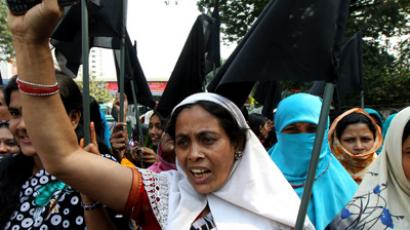 Bangladeshi garment workers shout slogans as they hold black flags during a protest in Dhaka on November 28, 2012 following a deadly fire in a garment factory (AFP Photo)