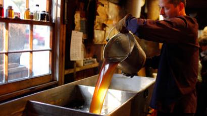 Steve Randle, a software engineer during the work-week, pours freshly made maple syrup in the finishing pan at Hollis Hills Farm in Lunenburg.(REUTERS / Brian Snyder)
