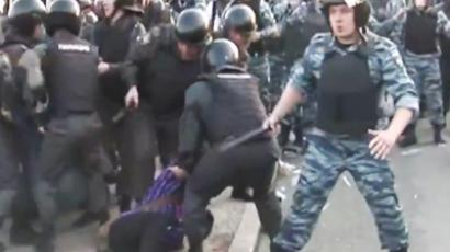Police officers drag away activist on Bolotnaya Square on May 6.