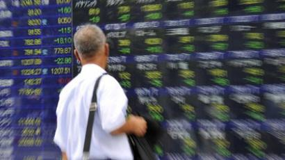 : A businessman watches a share prices board in Tokyo on August 8, 2011 (AFP Photo / Yoshikazu Tsuno)