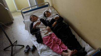Two Afghan schoolgirls lie on a bed in a hospital in Kabul, as they receive treatment for suspected poisoning at their school. (AFP Photo/Yuri Cortez)