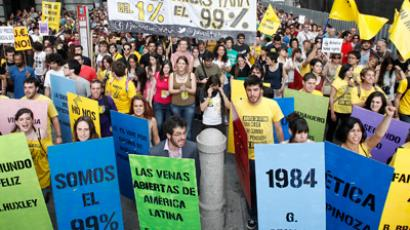 "Protesters hold up a banner which reads, ""Regime of the 1%, Crisis for 99%"", during a protest marking the one year anniversary of Spain's Indignados (Indignant) movement in Madrid's Puerta del Sol, May 12, 2012 (Reuters/Andrea Comas)"