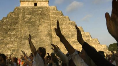 Visitors raise their hands during celebrations for the end of the Mayan cycle known as Bak'tun 13 and the start of the Maya new age, at the Chichen Itza archaeological park, in Yucatan state, Mexico on December 21, 2012. (AFP Photo/Pedro Pardo)