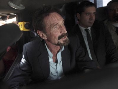 Software pioneer John McAfee is escorted by immigration officers at La Aurora International Airport in Guatemala City December 12, 2012. (Reuters/William Gularte)