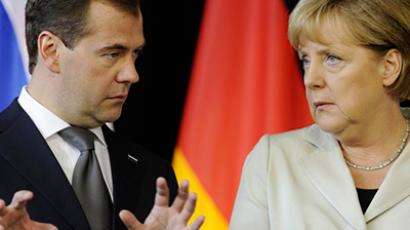 Russian President Dmitry Medvedev (L) and German Chancellor Angela Merkel talk at a signing ceremony after a round of German-Russian consultations in Hanover July 19, 2011 (AFP Photo / John Macdougall)