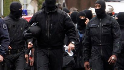 Masked French special unit policemen leave the scene after the assault to capture gunman Mohamed Merah during a raid on a five-storey building to arrest a suspect in the killings of three children and a rabbi on Monday at a Jewish school, in Toulouse March 22, 2012 (Reuters / Jean-Paul Pelissier)