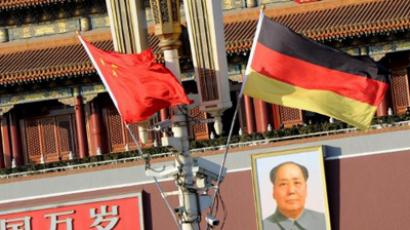 German and Chinese flags above a portrait of Chairman Mao in Tiananmen Square on the eve of a two-day visit by German Chancellor Angela Merkel, in Beijing on February 1, 2012 (AFP Photo / Mark Ralson)