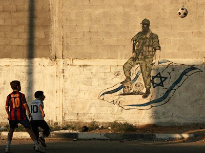 Palestinian boys play football in front of anti-Israeli graffiti in Gaza City on September 28, 2011 (AFP Photo / Mahmud Hams)