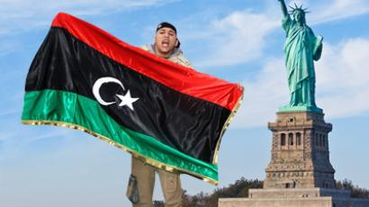 Arab man holding the flag of the Libyan opposition in front of the Statue of Liberty