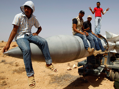 Anti-Gaddafi fighters sit on an SA-5 SAM missile in Burkan air defense military base	(Reuters / Goran Tomasevic)