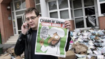 The Charlie Hebdo's publisher, known only as Charb, shows a special edition of French satirical magazine Charlie Hebdo on November 2, 2011 in Paris (AFP Photo / Alexander Klein)