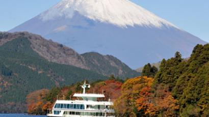 A sightseeing ship passes in front of Japan's highest peak, Mount Fuji, on Lake Ashinoko and other mountains covered with coloured autumn leaves at a Hakone hot spring resort, some 100 kms west of Tokyo. (AFP Photo / Toru Yamanaka)