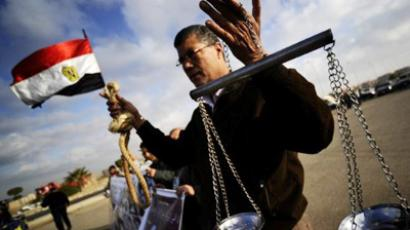 An Egyptian man holds a pair of scales and a noose as he protests against former President Hosni Mubarak ouside the Police Accademy where his trial is being held on the outskirts of Cairo on December 28, 2011 (AFP Photo / Filippo MONTEFORTE)