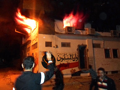 Egyptian protesters stand outside the burning office of the Muslim brotherhood in Ismailia, Egypt, on December 5, 2012 (AFP Photo / Stringer)