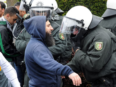 A man is inspected by policemen after he attended a demonstration called by ultra-conservative Muslims Salafist movement against the small extreme-right party Pro NRW on May 5, 2012 in Bonn. (AFP Photo / Henning Kaiser)