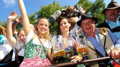 Germany, Munich : People dressed with traditional Bavarian clothes share a toast at the start of the Oktoberfest beer festival at the Theresienwiese ground in Munich, southern Germany, on September 17, 2011. (AFP Photo / Marc Mueller)