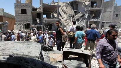 Libyans gathering on June 19, 2011 next to the rubble of buildings the Libyan authorities said were damaged by airstrikes on Tripoli's residential district of Arada (AFP Photo / Mahmud Turkia)