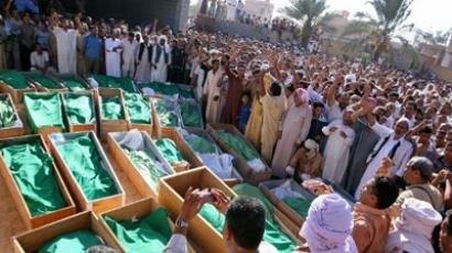 Libyan mourners gather around coffins during a mass funeral in the village of Majer (AFP Photo / Imed Lamiloum)