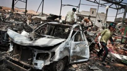 Libyans inspect the damage at a factory targeted by NATO air strikes (AFP Photo / Colin Summers)