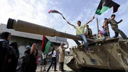 Libyans wave the revolution flag on top of a tank as weapons and other items belonging to the former regime are displayed in Misrata (AFP Photo / PHILIPPE DESMAZES)