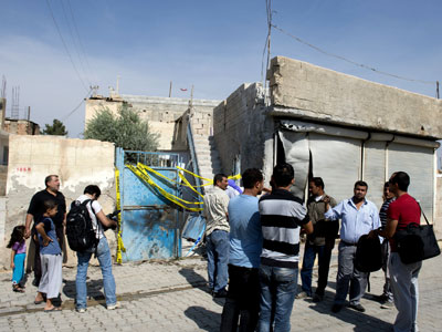 People gather on October 4, 2012, in front of the house where five people were killed after a mortar fired from Syria crashed inside the Turkish border town of Akcakale on October 3, killing five civilians, including a mother and her three children.(AFP Photo / Miguel Medina)
