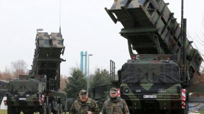 Soldiers of the Air Defence Missile Squadron 2 walk past Patriot missile launchers in the background in Bad Suelze, northern Germany  on December 4, 2012. (AFP Photo / Bernd Wustneck)