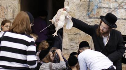 A ultra-Orthodox Jewish man holds a chicken over the heads of children as they perform the Kaparot ritual in Jerusalem's Mea Shearim neighbourhood September 23, 2012, ahead of Yom Kippur, the Jewish Day of Atonement. Kaparot is an ancient custom connected to Yom Kippur, where white chickens are slaughtered as a symbolic gesture of atonement. (Reuters/Ammar Awad)