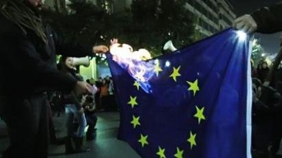 Demonstrators burn an EU flag during a protest in Thessaloniki on November 17, 2011 (AFP Photo/Sakis Mitrolidis)