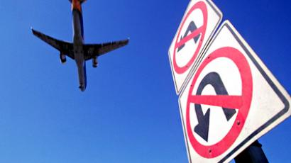 Airplane over directional signs