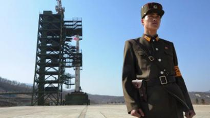 A North Korean soldier stands guard in front of an Unha-3 rocket at Tangachai -ri space center on April 8, 2012 (AFP Photo / Pedro Ugarte)