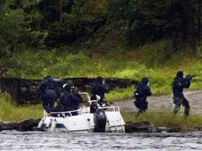 A swat team aim their weapons while people take cover during a shoot out at Utoeya island, some 40 km south west of the capital Oslo on July 22, 2011 (AFP Photo / Jan Bjerkeli)