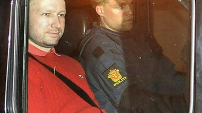 Bomb and terror suspect Anders Behring Breivik (red top) leaves the courthouse in a police car in Oslo on July 25, 2011, after the hearing to decide his further detention (AFP Photo / Jon-Are Berg-Jacobsen / Aftenposten)