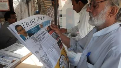 Pakistan, Karachi: A Pakistani man reads a newspaper with the front page displaying news of the death of Osama bin Laden at a stall in Karachi on May 3, 2011. (AFP Photo / Rizwan Tabassum)