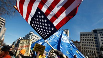 An Occupy DC demonstrator waves a flag in McPherson Square in Washington January 30, 2012 (Reuters / Kevin Lamarque)