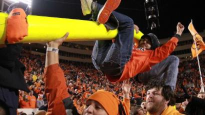 Video from okstate73 YouTube channel. Image: Oklahoma State Cowboys fans hang on the goalpost after a 44-10 win against the Oklahoma Sooners at Boone Pickens Stadium on December 3, 2011 in Stillwater, Oklahoma (Ronald Martinez/Getty Images/AFP)
