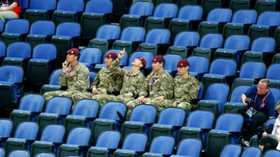 Soldiers sit in the empty seats held by the IOC as they watch the women's gymnastics qualification in the North Greenwich Arena during the London 2012 Olympic Games July 29, 2012 (Reuters / Mike Blake)