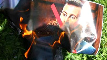 Turkey, Ankara : Men protesting Syrian President Bashar al-Assad's regime burn a portrait of him as they demonstrate in front of the Syrian embassy in Ankara, while other groups nearby demonstrate to express support for the Syrian regime, on June 10, 2011. (AFP Photo / Adem Altan)