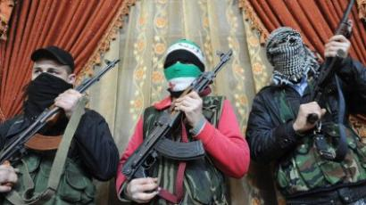 Armed Free Syrian Army rebels stand inside a house in the north Syrian city of Binnish (AFP Photo / Bulent Kilic)