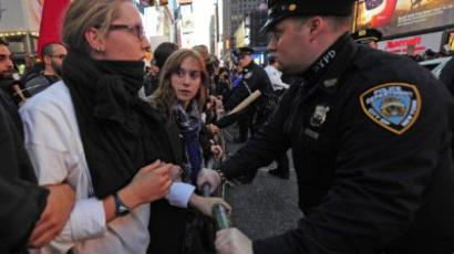 New York : Occupy Wall Street participants link arms to try to push trough police barricade as the authorities stop them to take their demonstration onto the street on Times Square in New York. (AFP Photo/Emmanuel Dunand)