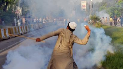 A Pakistani Muslim protester throws a tear gas shell back towards police as demonstrators attempt to reach the US embassy during a protest against an anti-Islam film in Islamabad on September 20, 2012 (AFP Photo / Aamir Qureshi)